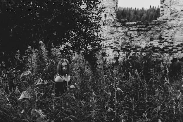 Monochromer düsterer blick auf die ruinen und die frau eines zombies oder einer hexe unter hohem gras
