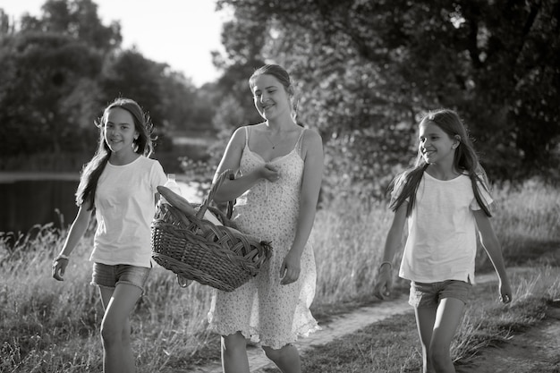 Monochromes bild der glücklichen mutter mit töchtern, die auf der wiese spazieren gehen