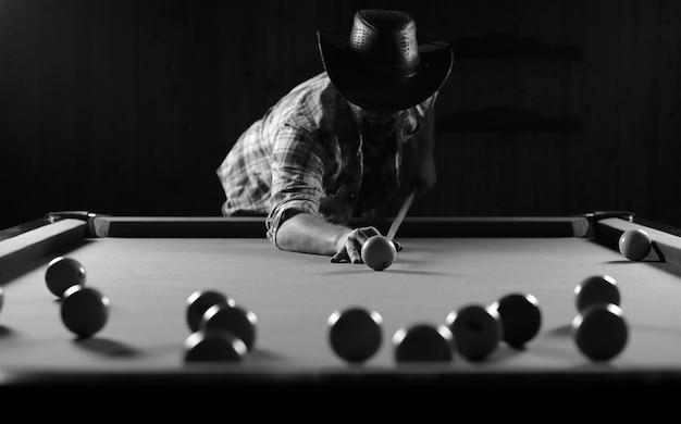 Monochromes foto eines jungen mannes, der billard spielt