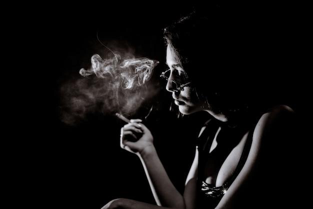 Monochromes porträt des jungen mädchens, das mit großem dekolleté und in brillen raucht