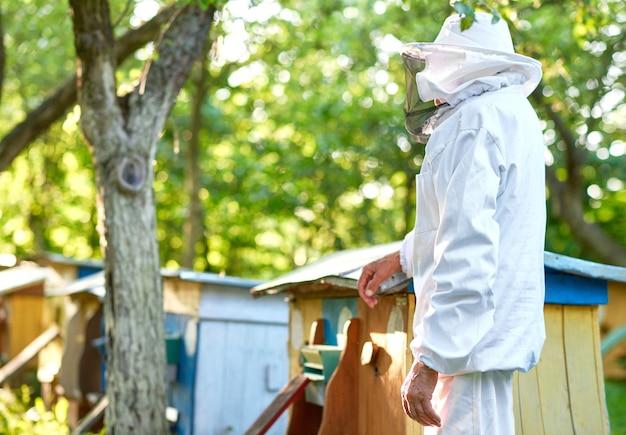 Monochromes porträt eines älteren mannes, der bienenzuchtanzug trägt, der an seinem bienenhaus in der gartenkopyspaceberufsberufslandwirtlandwirtschaftsjob-hobby-lebensstilkonzept aufwirft.