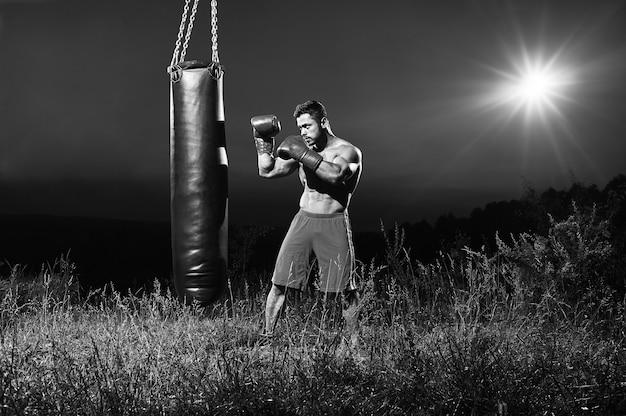 Monochromes porträt eines gutaussehenden jungen muskulösen männlichen boxers, der nachts im freien trainiert und auf einem boxsack-kopierraum übt.