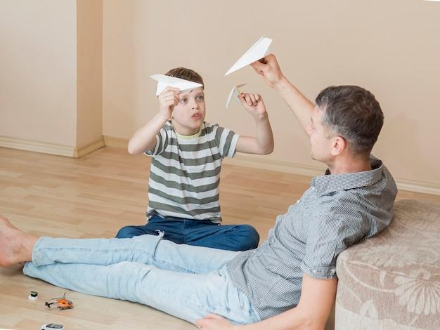 Monoparentaler vater und kind spielen mit papierflugzeugen