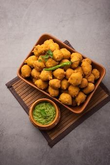 Monsunspezial moong dal vada, pakoda, dalwada, pakora oder mungdal bhajiya oder yellow split gram fritters, serviert mit grünem chutney Premium Fotos