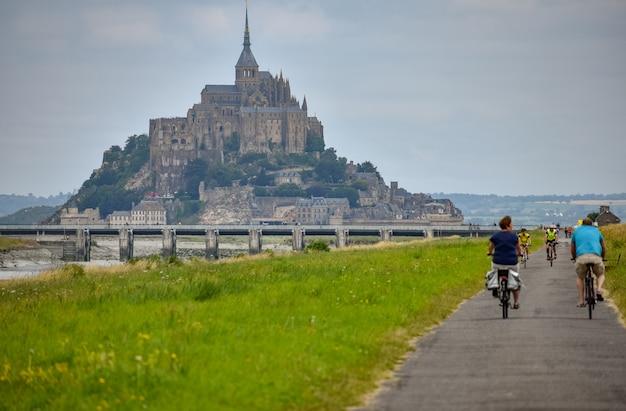 Mont saint-michel, frankreich - 3. juli 2017: radfahrer gehen an einem sommertag zu mont saint-michel, einem der wichtigsten touristischen ziele in der französischen normandie.
