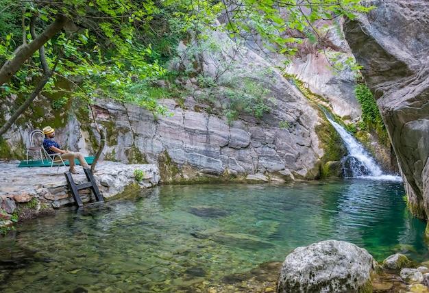 Montenegro - 30. mai 2017: der tourist genießt den blick auf den kleinen malerischen wasserfall.