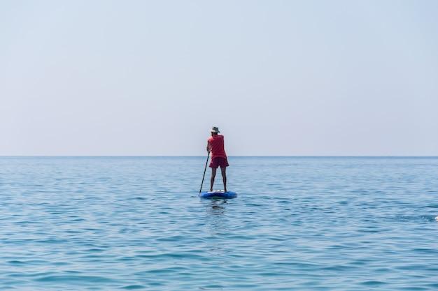 Montenegro budva-touristen rudern auf dem sup-board auf der oberfläche der ruhigen see