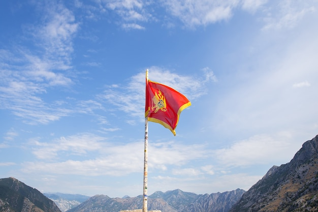 Montenegro-flagge vor dem hintergrund eines wunderschönen blauen himmels mit im wind flatternden wolken.