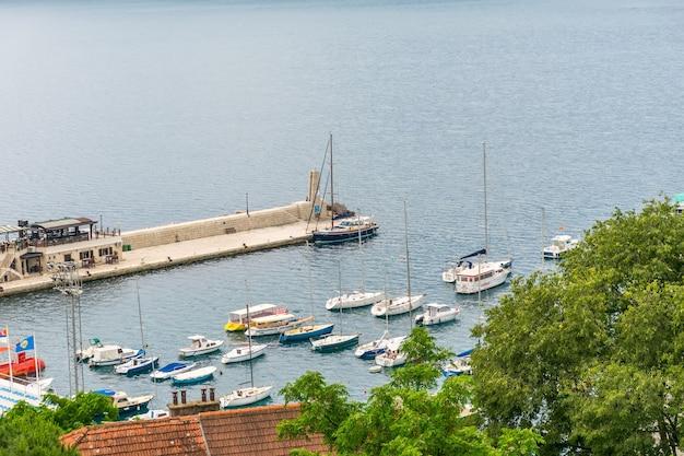 Montenegro, herceg novi. reisende parken ihre schiffe auf einer vorinsel nahe der stadtküste.