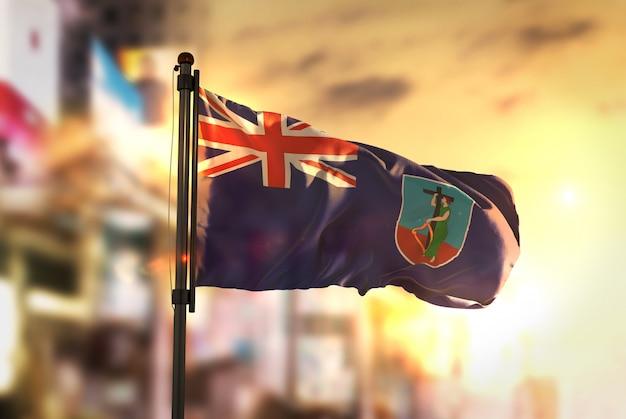 Montserrat-flagge gegen stadt verschwommen hintergrund bei sonnenaufgang hintergrundbeleuchtung