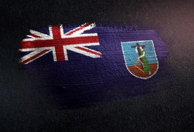 Montserrat-flagge gemacht von der metallischen bürsten-farbe auf schmutz-dunkler wand
