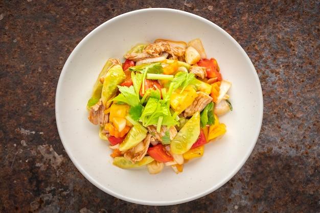 Moo pud preaw wan, thailändisches essen, süß-saure soße gebraten mit schweinefleisch, ananas, tomate, gurke, zwiebel mit sellerie in keramikplatte auf rostigem texturhintergrund, draufsicht