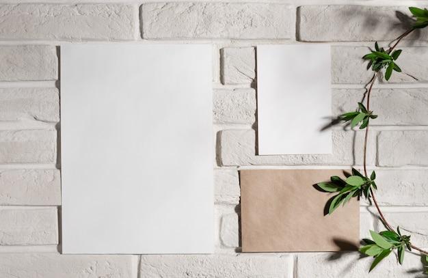 Moodboard-vorlagenzusammensetzung mit leeren papierkarten auf weißer backsteinmauer mit grünem zweig