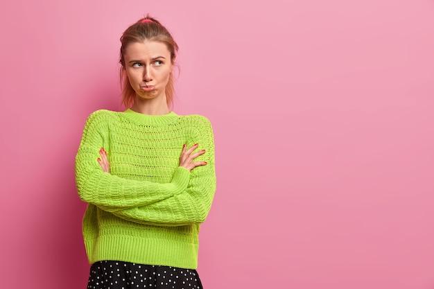 Moody beleidigte frau steht mit gekreuzten händen, spitzt die lippen, ist beleidigt, schaut unter der stirn hervor, trägt einen grünen pullover, steht über rosa wand