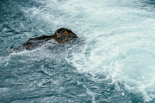 Moosiger stein im azurblauen wasser der gebirgsflussnahaufnahme.