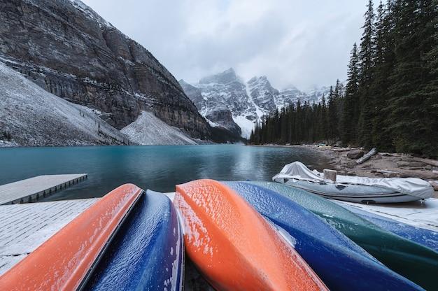 Moränensee mit felsigen bergen im düsteren und bunten kanu auf dem pier im banff-nationalpark, kanada
