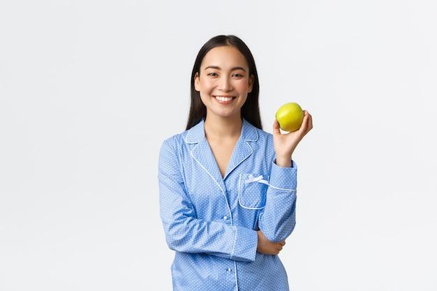 Morgen, aktiver und gesunder lebensstil und wohnkonzept. ein apfel hält ärzte fern. fröhliches süßes asiatisches mädchen im blauen pyjama, das apfel zum frühstück isst und freudige, weiße wand lächelt.