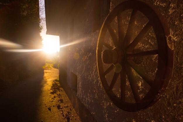 Morgen auf einem bauernhof im dorf. kleine straße und morgenstrahlen. holzrad vom karren im vordergrund