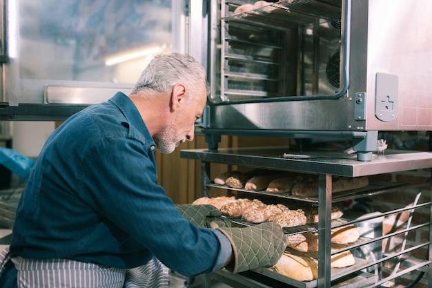 Morgen baguettes. bärtiger erfahrener bäcker, der aufgeregt ist, bevor er schöne morgenbaguettes backt