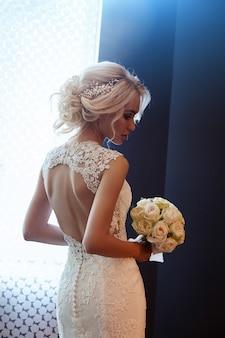 Morgen braut. eine frau in einem weißen hochzeitskleid, das einen blumenstrauß in ihren händen hält. schönes blondes mädchen, das zur hochzeitszeremonie fertig wird