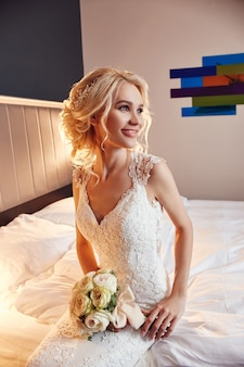 Morgen braut. eine frau in einem weißen hochzeitskleid, das einen blumenstrauß in ihren händen hält.