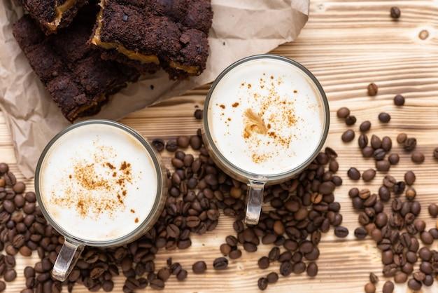 Morgen cappuccino mit schokoladenkuchen. auf einem holztisch mit kaffeebohnen.