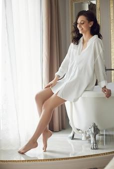 Morgen der braut. eine schöne frau bereitet sich auf eine hochzeit, natürliches make-up und eine schicke frisur vor. weißes peignoir und das hochzeitskleid