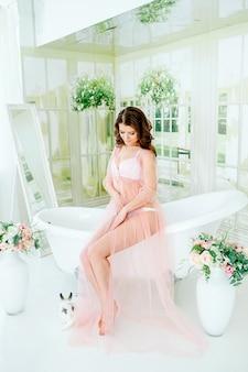 Morgen der braut. frau kleidete in einem transparenten boudoirkleid und -unterwäsche, in einem weinlesebadezimmer, nahe einem weißen kaninchen an