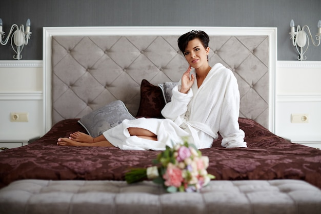 Morgen der braut im schlafzimmer, in einem weißen gewand auf dem bett liegend mit einem blumenstrauß.