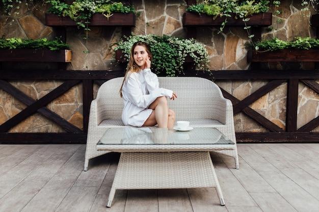 Morgen der braut, schöne blonde frau im hemd eines mannes auf der terrasse des sommercafés. hochzeitskonzept.