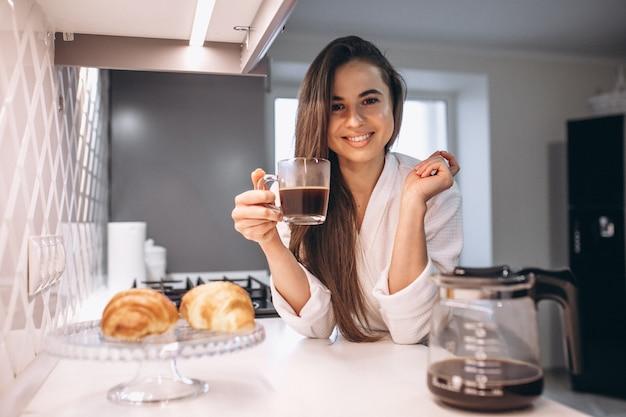 Morgen der frau mit kaffee und hörnchen