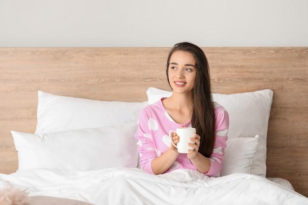 Morgen der schönen jungen frau, die kaffee im bett trinkt