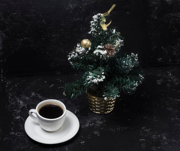Morgen duftender schwarzer kaffee mit weihnachtsbaum, weihnachtsmorgen.