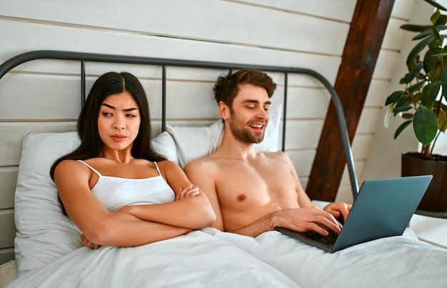 Morgen eines jungen paares. ein muskulöser mann benutzt einen laptop, und eine koreanerin wendet sich von ihm ab und ist wütend, aufgebracht, unzufrieden.