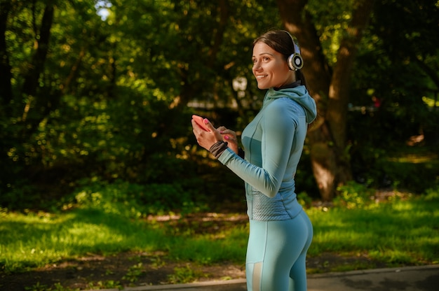 Morgen fitness-training im park, lächelnde frau in kopfhörern