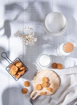 Morgen frische hausgemachte haferkekse auf schneidebrett mit glas milch auf einem weißen holztisch