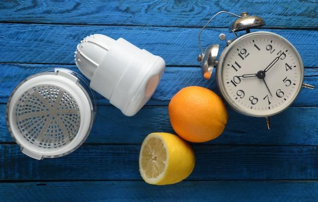 Morgen frischer saft aus zitrone und orange. handgemachter entsafter, wecker, zitrusfrucht auf einem blauen hölzernen hintergrund. draufsicht.