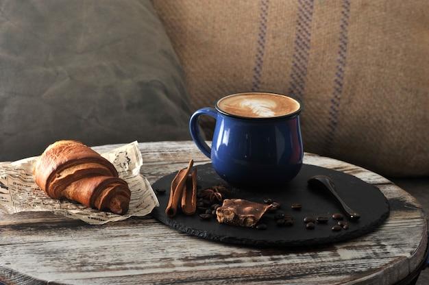 Morgen-frühstück am cafécappuccino in einem becher mit milchschaum und einem hörnchen