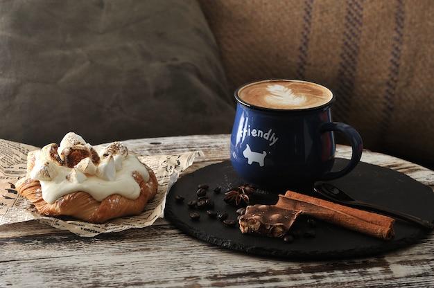 Morgen-frühstück am cafécappuccino in einem becher mit milchschaum und in einem schokoladenkuchen mit sahne und in den eibischen
