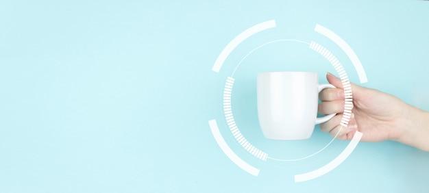 Morgen herunterladen. mädchenhand halten morgenkaffeetasse mit mock-up-kreisdiagramm. platz kopieren. blauer hintergrund.