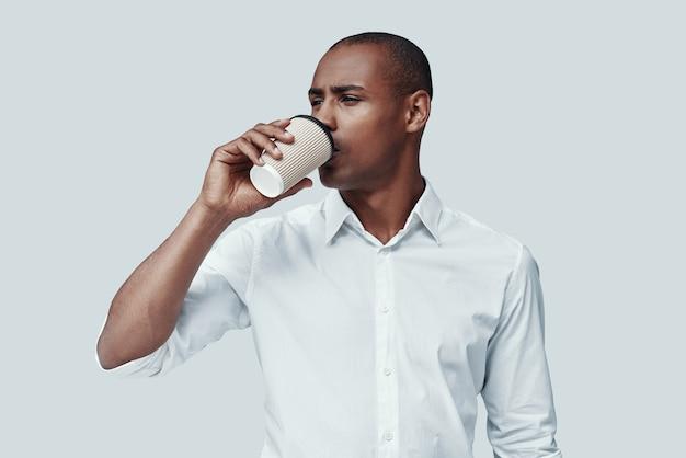 Morgen kaffee. hübscher junger afrikaner, der kaffee trinkt, während er vor grauem hintergrund steht