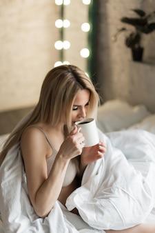 Morgen mädchen die blondine mit einer tasse tee kaffee frühstück im bett ich bin gerade aufgewacht