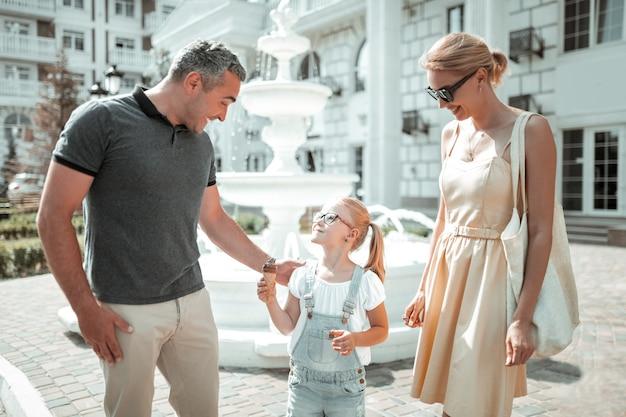 Morgen mit einer familie. glückliche familie, die während ihres morgenspaziergangs vor dem schönen brunnen zusammensteht.