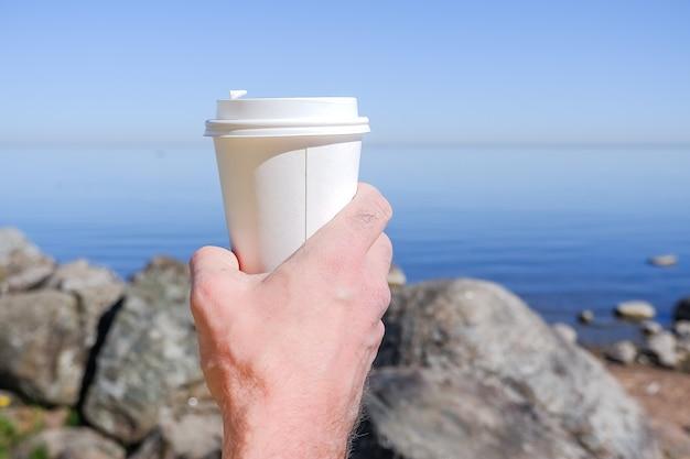 Morgen papier kaffeetasse mit leckerem heißem kaffee in der hand im freien auf deich.hand hält einen weißen papppapierbecher für getränke zum mitnehmen, gegen schöne meeresmauer, umgebung