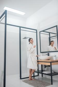 Morgen prozeduren. ein bild einer jungen frau im bademantel im badezimmer