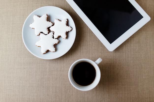 Morgen tasse kaffee auf dem schäbigen weißen schreibtisch mit digitaler tablette mit leerem bildschirm, kerze, frischem keks