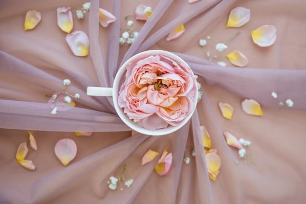 Morgen tasse kaffee mit schönen rosenblüten auf rosa stoff zarten pastellblumen