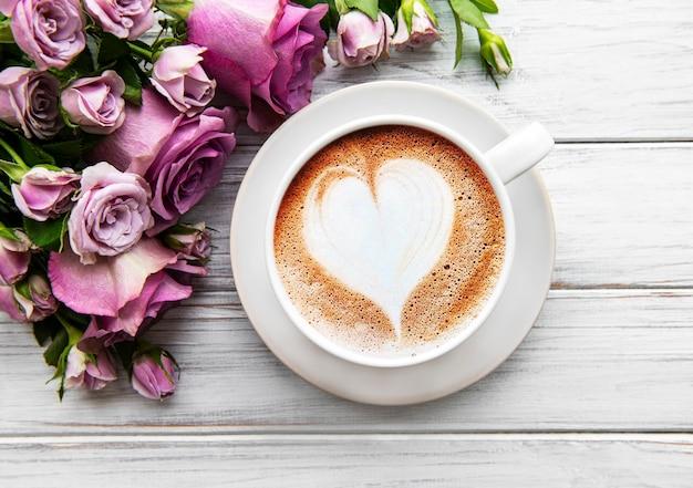 Morgen tasse kaffee und schöne rosenblumen auf einem hellen hintergrund, draufsicht. gemütliches frühstück. flach liegen