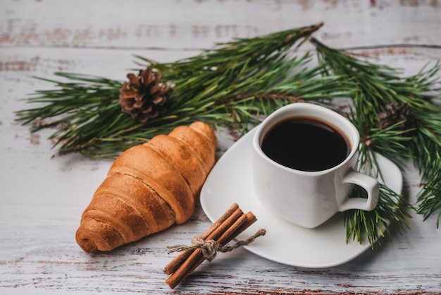 Morgen-weihnachtsfrühstück mit einem tasse kaffee und einem hörnchen auf einem holztisch