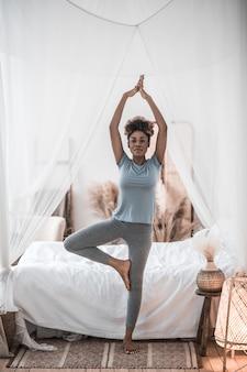 Morgen yoga. glückliche junge erwachsene dunkelhäutige frau mit erhobenen armen und gebogenem knie, das im schlafzimmer steht und yoga tut